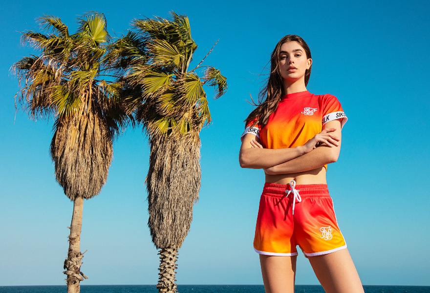 Weibliches Model ist rot-orangem Shirt und Shorts von SikSilk