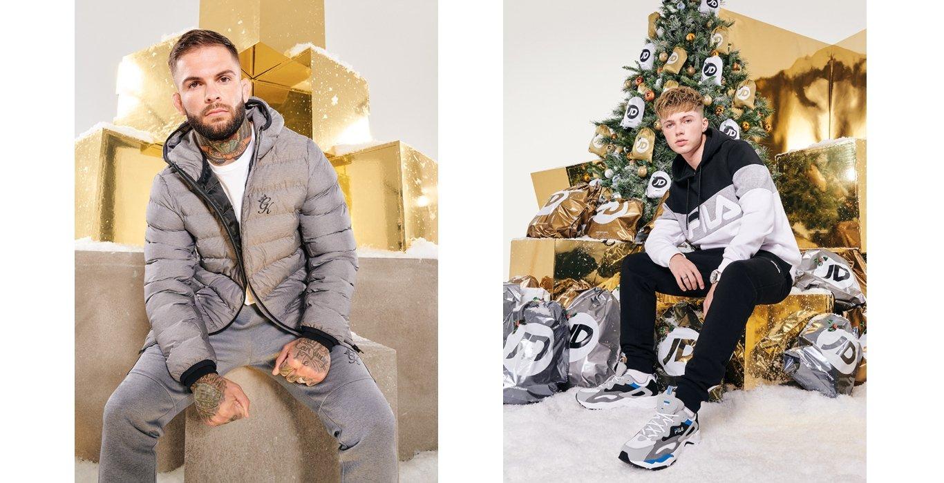 Zwei männliche Models vor Weihnachtsgeschenken und Weihnachtsbaum