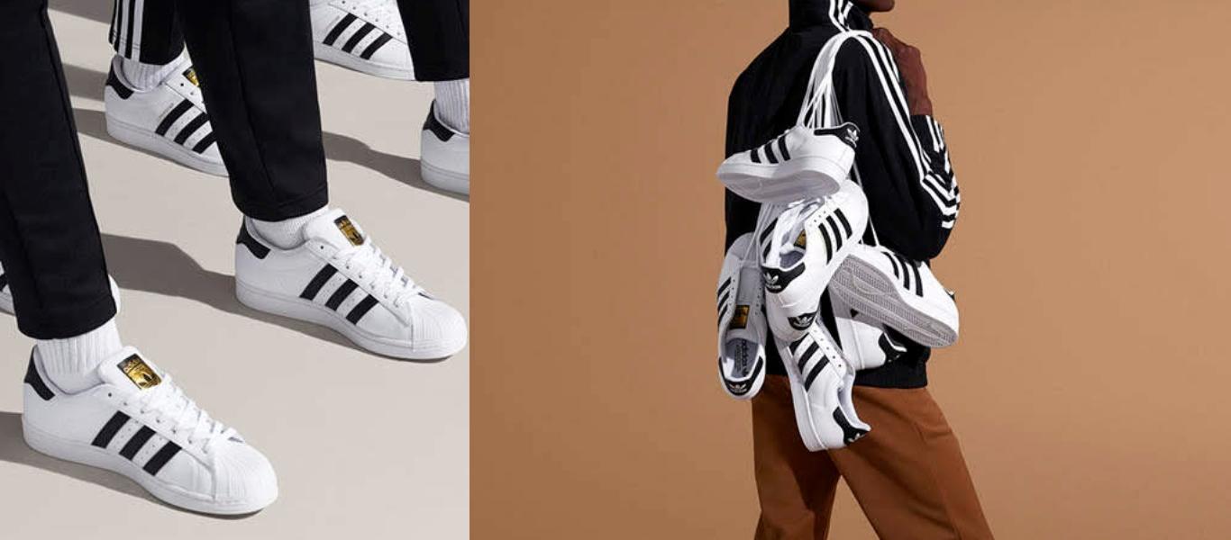 der adidas Originals Superstar in Weiß, rechts am Fuß, links mehrere über die Schulter geworfen